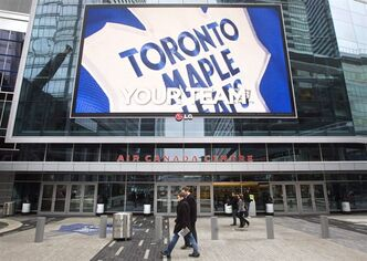 Pedestrians walk past the Air Canada Centre as a screen projects an image of the Toronto Maple Leafs logo in Toronto Wednesday, December 1, 2010. A report says the NHL lockout is forcing Canadian merchants near hockey arenas into the penalty box, with spending down more than 11 per cent from a year ago on a game day.THE CANADIAN PRESS/Darren Calabrese