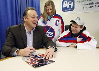 Former Winnipeg Jets captain Dale Hawerchuk signs autographs for Andrew and Jessica Szun during a corporate promotion he was doing at BFI in Winnipeg on Monday.