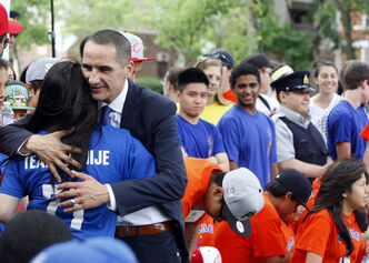 A student gets a hug from Kevin Chief at the youth jobs announcement.