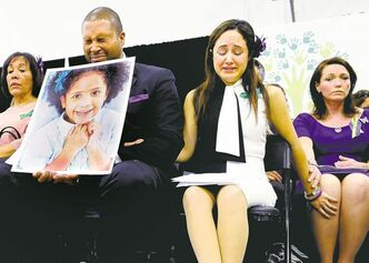 Jessica Hill / The Associated Press Jimmy Greene holds a photo of his slain daughter, Ana, as his wife Nelba Márquez-Greene (centre) and Nicole Hockley, mother of victim Dylan Hockley, comfort each other at Monday's news conference.