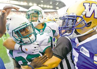 Roughriders' Tristian Jackson (38) and Bombers' Demond Washington (right) have to be separated on the Bomber sidelines as tempers flare during the Banjo Bowl Sunday.