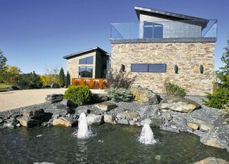The backyard offers beautiful scenery, mountains of stone and rock, as well as a pond and a swimming pool.