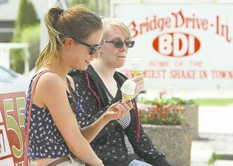 Britney Bell (left) and Kaeley Gould enjoy ice cream at the Bridge Drive-In on Saturday.