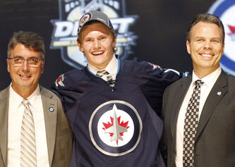 Defenceman Jacob Trouba (center) stands with Winnipeg Jets head coach Claude Noel and general manager Kevin Cheveldayoff after being chosen ninth overall in the 2012 NHL hockey draft in Pittsburgh.