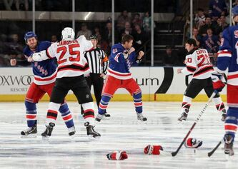 New York Rangers' Brandon Prust (left) fights New Jersey Devils' Cam Janssen and Rangers'Stu Bickel (41) dukes it out with Ryan Carter (20) of the Devils three seconds into the game on Monday at Madison Square Garden in New York.