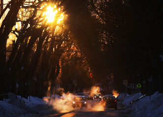 Cars kick up exhaust fog during a cold and colourful sunrise this morning on Kingsway Avenue in River Heights.