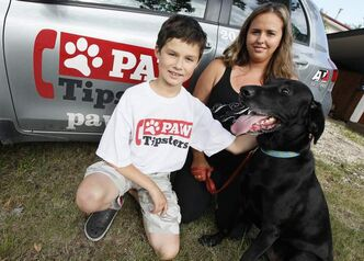 Paw Tipsters president Yvonne Russell, with volunteer Joel and rescue dog Gary, seeks donations.