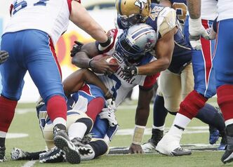 Montreal's Adrian McPherson (3) is sacked by Henoc Muamba (10) and Rodney Fritz (45) during the first half of the game Saturday.