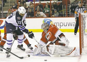 Dustin Byfuglien jams the Hurricanes net during a Winnipeg Jets power play in in Raleigh, N.C., on Thursday.