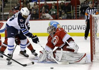 Carolina Hurricanes goalie Cam Ward defends the goal while Winnipeg Jets defenceman Dustin Byfuglien tries to score during the first period of an NHL game in Raleigh, N.C., Thursday.