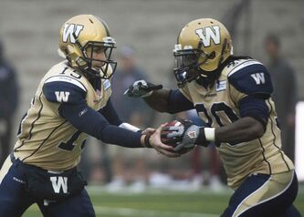 Winnipeg Blue Bombers' quarterback Max Hall, left, hands off to Will Ford during first half CFL football action against the Montreal Alouettes in Montreal, Monda.