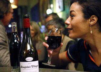 Nora Boutemeur enjoys a glass of Beaujolais Nouveau in Lille, northern France, Thursday, Nov. 21, 2013. The wine world's best-known party is beginning, the ritual uncorking of Beaujolais Nouveau every November. That's both a curse and a blessing for the famed French region and its lesser-known yet finer wines.