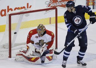 Winnipeg Jets' Blake Wheeler (26) deflects the shot from the point for the goal agaist Florida Panthers goaltender Jacob Markstrom during first-period NHL action in Winnipeg on Friday.