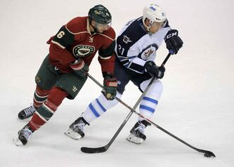 Minnesota Wild's Marco Scandella, left, and Winnigeg Jets' Jerome Samson, right, go after the puck in the first period of an NHL hockey game on Saturday, Sept. 21, 2013, in St. Paul, Minn. (AP Photo/Tom Olmscheid)