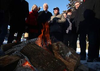 Members of Parliament gather around a bonfire in sub zero weather as they wait to meet with Attawapiskat First Nations Chief Theresa Spence in Ottawa, Sunday.