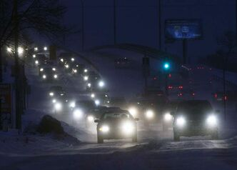 Cars crawl over the Slaw Rebchuk overpass Wednesday morning as driving conditions were tricky with the 5 cm of snow that fell overnight in Winnipeg.