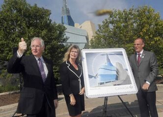 CMHR President and CEO Stuart Murray gives a thumb's up at the unveiling of a new stamp issued to mark the opening of the Canadian Museum for Human Rights next month. MP Shelly Glover (St. Boniface) and Canada Post Vice President Bill Davidson (right) also attended.