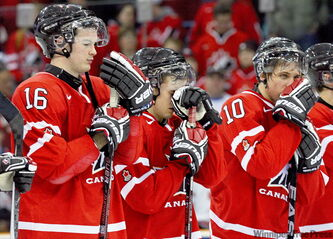 Dejected Team Canada players, in­cluding Greg Nemisz (16) and Brayden Schenn (10) watch Team USA receive the trophy after the Americans won the gold medal game of the World Junior Hockey Champion­ships in Saskatoon on Tuesday night.
