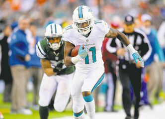 Miami Dolphins' Mike Wallace (11) breaks free for a touchdown past New York Jets' Dee Miller on Sunday afternoon.