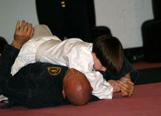 This June 2010 photo provided by Lisa Suhay shows her son Quin Suhay, now 8, tackling Bill Odom, owner of Norfolk Karate Academy in Norfolk, Va., as part of a bullyproofing class that combines jujitsu _ defensive moves only, no punching or kicking _ with verbal strategies. Other types of bullyproofing programs, including guides for parents and regular classroom curricula, seek to make kids less vulnerable to being picked on by teaching them how to deal with teasing and how to make friends. (AP Photo/Lisa Suhay)