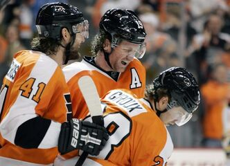 Philadelphia Flyers' Scott Hartnell, center, celebrates his second goal of the period along with teammates Andrej Meszaros (41) and Claude Giroux (28) during the second period of an NHL hockey game against the Boston Bruins on Sunday, Jan. 22, 2012, in Philadelphia. Hartnell has been added to the NHL all-star roster for this weekend's game in Ottawa. THE CANADIAN PRESS/AP-Tom Mihalek