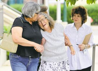 A grieving Anne Lacquette, grandmother of Duane Lacquette is helped down the Brandon courthouse steps Thursday.