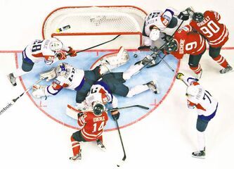 The puck lies a few inches from the goal-line as Team Canada and Slovenia scramble around the net during third period Monday.