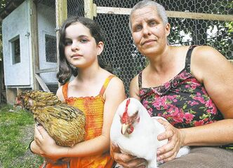 Mike Deal / Winnipeg Free PressStacie Gottfried with her daughter, Shanti, and two of the five hens, Jumpy (left) and Ono (right), they have in a backyard coop.