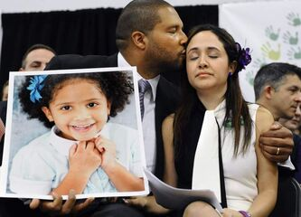 Jimmy Greene kisses his wife, Nelba Márquez-Greene, as he holds a portrait of their daughter, Ana Márquez-Greene, at a news conference in Newtown, Conn., one month after the mass school shooting.