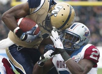 Winnipeg Blue Bombers' Cory Watson, left, is tackled by Montreal Alouettes' Mike Edem during first half CFL football action in Montreal Monday.