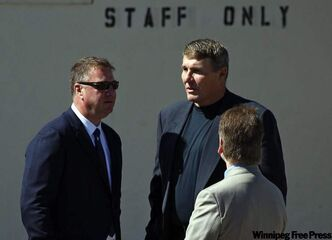 Former NFL quarterback Mark Rypien, centre, talks with Vancouver Canucks general manager Mike Gillis, while attending the funeral service for his cousin Rick Rypien, 27, in Blairmore, Alta., Saturday. Rypien was found dead in his off-season Coleman, Alta., home on Aug. 15. He had just signed with the Winnipeg Jets last month after six seasons with the Vancouver Canucks.