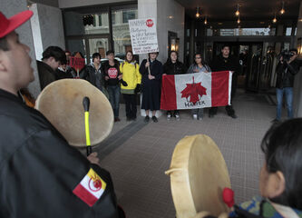 About 30 protesters showed up outside the Delta Inn for PM Harper's visit.