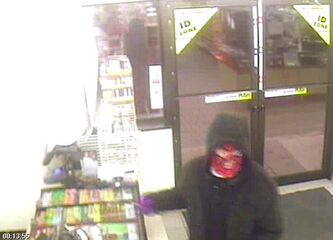 Picture from video surveillance shows masked man in act of robbing store.