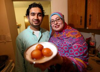 Mohammad Haider (left) and Lubna Usmani display the gulab jamun they made for Sunday's Islamic Culture Day.