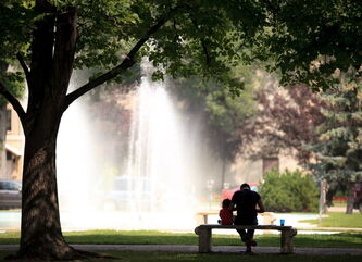 Father and son take shade under a tree in front of the fountain at Memorial Park on Friday afternoon.