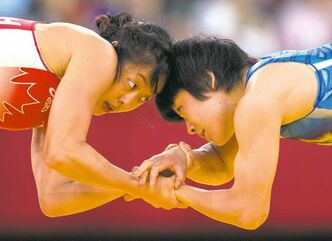 Canada 's Carol Huynh (red) locks arms with Hitomi Obara of Japan in the semi-final 48kg Women's Freestyle Wrestling at the Olympic Games in London on Wednesday August 8, 2012.
