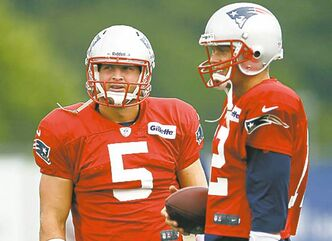 New England Patriots football quarterbacks Tim Tebow (5) and Tom Brady stand together during team practice in Foxborough, Mass., Monday, Aug. 26, 2013. (AP Photo/Elise Amendola)