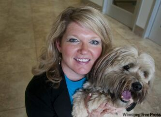Aileen White (probably gingerly) holds Barkley, a recently neutered dog.
