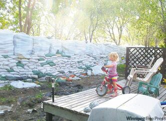 A young girl plays on a deck in the shadow of a huge dike protecting her family's home at Willow Bay.