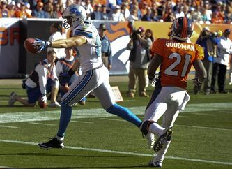 Detroit Lions tight end Tony Scheffler (85) reaches across the goal line to score a touchdown as Denver Broncos cornerback Andre' Goodman (21) tries to defend during the second quarter of an NFL football game on Sunday, Oct. 30, 2011, in Denver. (AP Photo/Joe Mahoney)