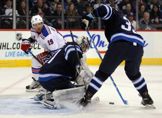 Winnipeg Jets goaltender Ondrej Pavelec and defenceman Dustin Byfuglien prevent a shot from New York Ranger Brad Richards (19) from entering the net in the first period of an NHL game at the MTS Centre Thursday night. The Jets downed the Rangers 3-1.