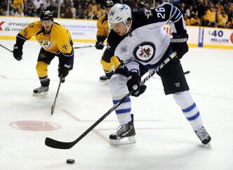 Winnipeg Jets' right winger Blake Wheeler controls the puck as Nashville Predators' defenceman Ryan Ellis closes in on him Saturday in Nashville.