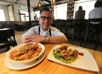 Executive chef/partner Norm Pastorin with chicken wings, left, and steak bites.