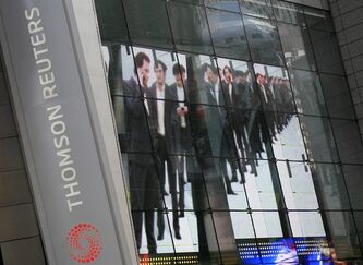 FILE - In this Aug. 4, 2009 file photo, electronic display advertising is shown on the Thomson Reuters building in New York. News and financial information company Thomson Reuters on Wednesday, Feb. 13, 2013, said it's cutting 2,500 jobs, or about 4 percent of its workforce, this year as it tries to reduce costs and turn around its largest division. (AP Photo/Mark Lennihan, file)