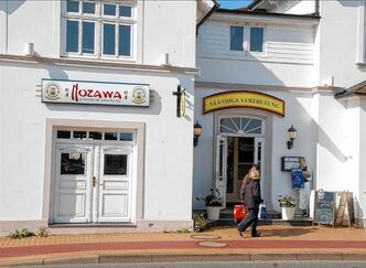 FILE - In this May 13, 2013 file picture, persons pass the restaurant 'Nozawa', left, in Westerland on the German North Sea island of Sylt. Authorities in Germany said Friday May 17, 2013 they are investigating a Japanese chef's death following a fight with two customers who had complained about his food. Prosecutors say Miki Nozawa died Monday May 13, 2013 following a brawl with the two men at a nightclub near his restaurant on the North Sea resort island of Sylt. German tabloid newspaper Bild reported the men had refused to pay for a dish of fried rice with vegetables and beef. The paper said Nozawa was a