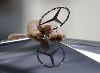In this July 16, 2009 file photo, an employee of the Daimler AG mounts the Mercedes star on the hood of a car of the Mercedes-Benz E-class on the production line in the Mercedes-Benz site in Sindelfingen, Germany. (AP Photo/Thomas Kienzle, File)