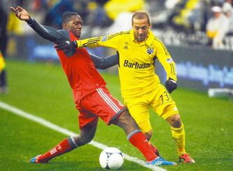 Toronto FC defender Doneil Henry (red) tries to stop Columbus (Ohio) defender Federico Higuain. Aside from Toronto, MLS teams are actually fun to watch.