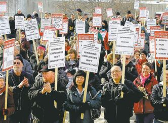 Protesters hold signs decrying University of Manitoba policies as they rally on the U of M campus Wednesday.