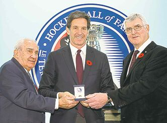 Brendan Shanahan is given his Hockey Hall of Fame ring by Chairman Pat Quinn (right) and chairman of the selection committee Jim Gregory.