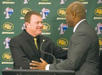 Eskimos GM Ed Hervey (right) congratulates new head coach Chris Jones at a news conference Wednesday.